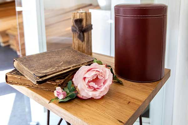 Rosa rose, altes Notizbuch und lederne Urne auf einem kleinen Holztisch